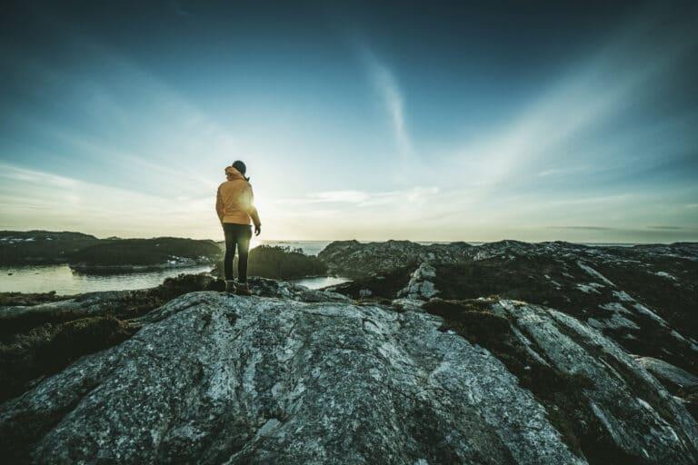 Mann som står og ser ut over et fjordlandskap.