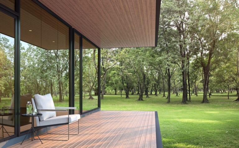 Terrasse ved et moderne hus i grønne omgivelser.