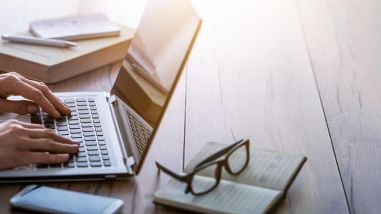 En person jobber på en laptop som står på et bord av tre.