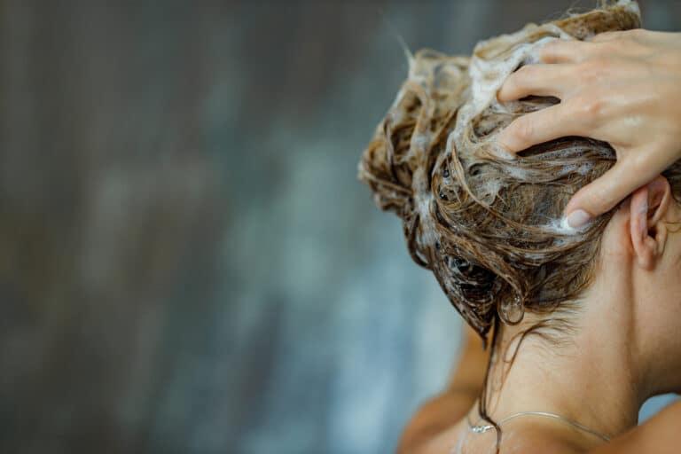 Kvinne som vasker håret med sjampo