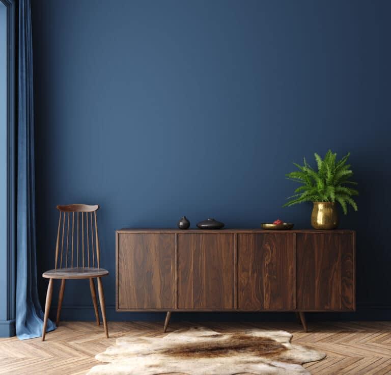 Interiørbilde, blå vegg med tremøbler foran.