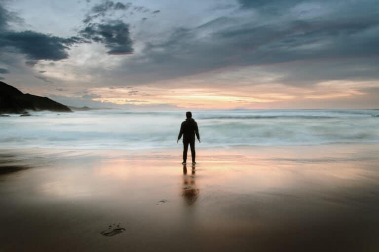 Mann som står på ei strand og ser utover.