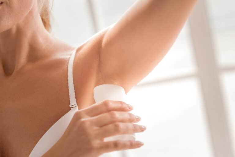 Kvinne som tar på deodorant.